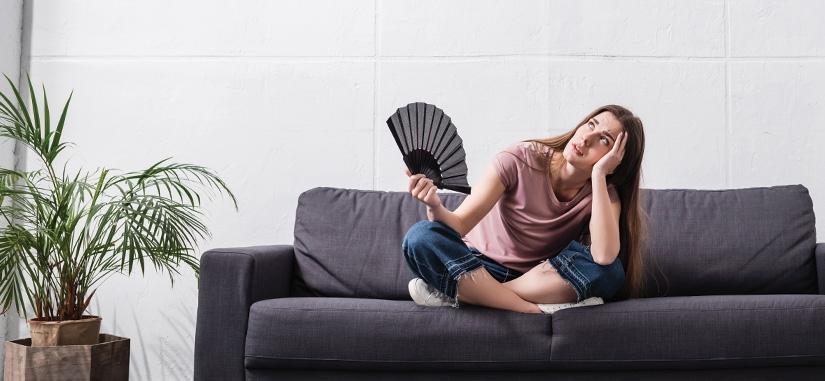 Femme sur son canapé qui a chaud