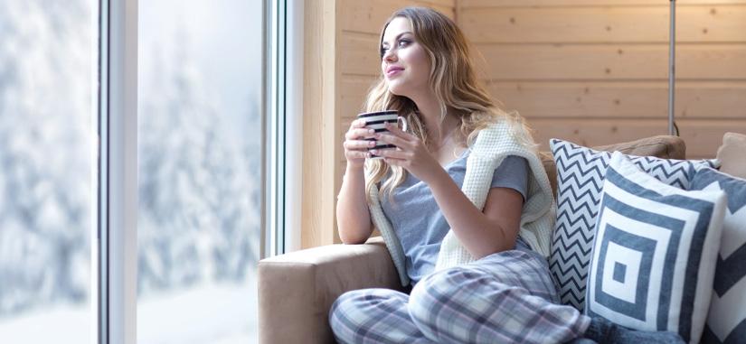 jeune femme regardant par la fenetre avec une tasse de the