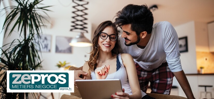 Un couple assis à une table en train de sourire en regardant une tablette