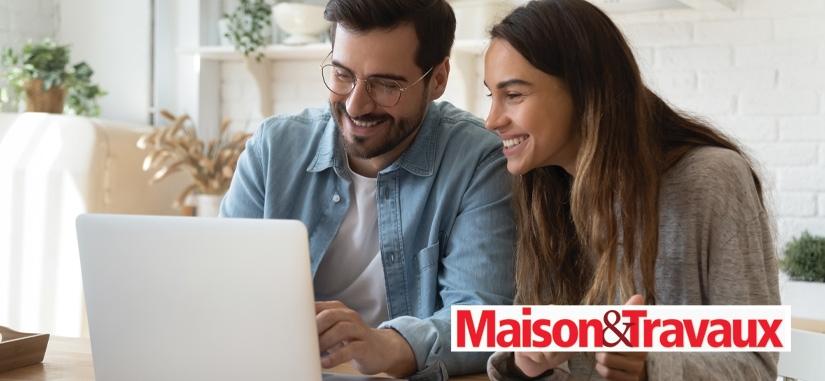 un couple assis à une table en train de regarde leur ordinateur