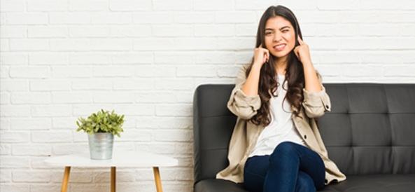 Femme sur son canapé qui se bouche les oreilles