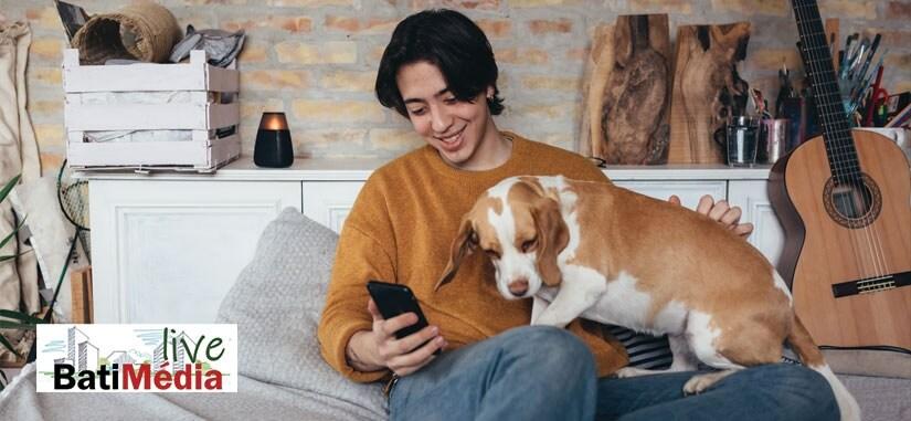 jeune homme qui regarde son téléphone avec son chien