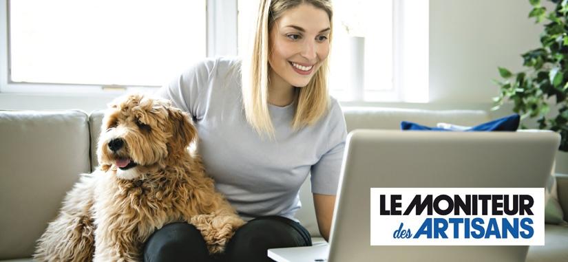 jeune femme assise sur son canapé qui regarde son ordinateur avec son chien à coté